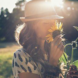 Frau mit Hut riecht an Sonnenblume